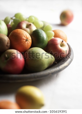 a bowl of fruit with fruit spilling over onto white background - stock photo