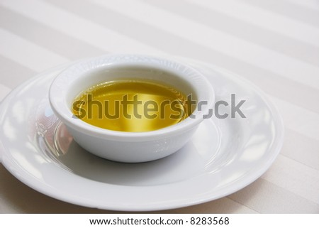 A bowl of golden olive oil sits on a white table cloth in a formal setting.