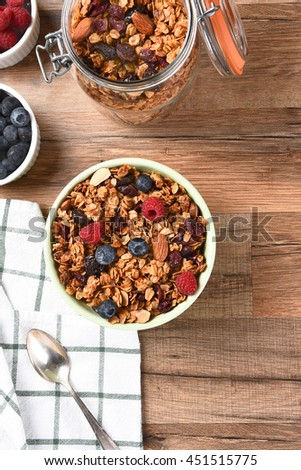 A bowl of Granola cereal with fresh fruit. Vertical with copy space. - stock photo