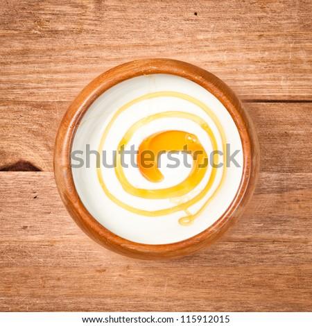 A bowl of greek yogurt with honey - stock photo