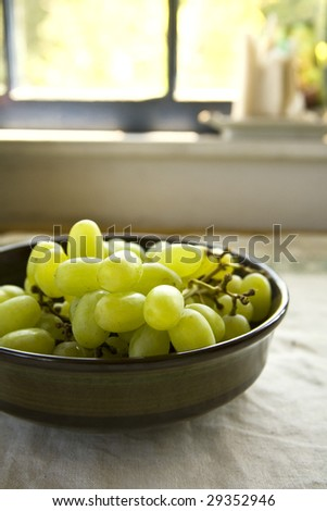 A bowl of green grapes sits on a table by a kitchen window. - stock photo