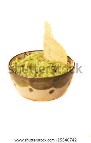 A bowl of guacamole with a chip - stock photo