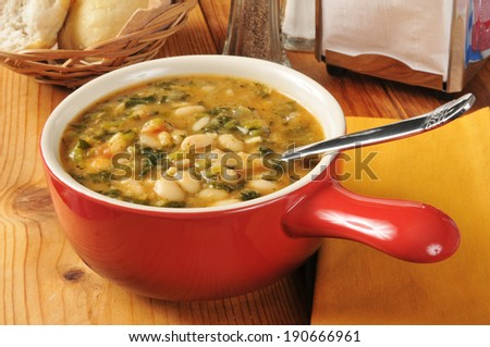 A bowl of healthy kale and white bean soup with dinner rolls - stock photo