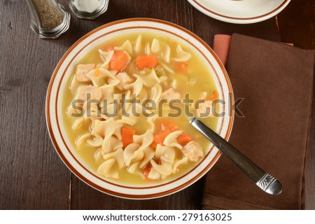 A bowl of hearty chicken noodle soup shot from overhead - stock photo