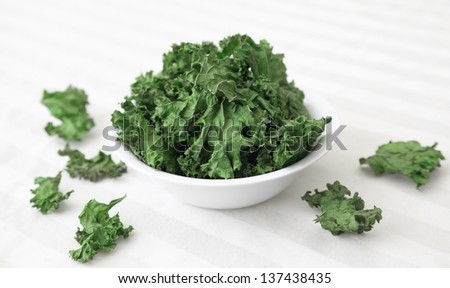 A bowl of home-made kale chips sitting on a table. - stock photo