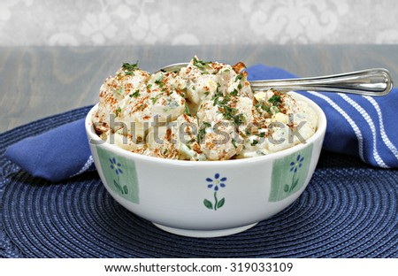 A bowl of homemade egg potato salad garnished with parsley and paprika. - stock photo