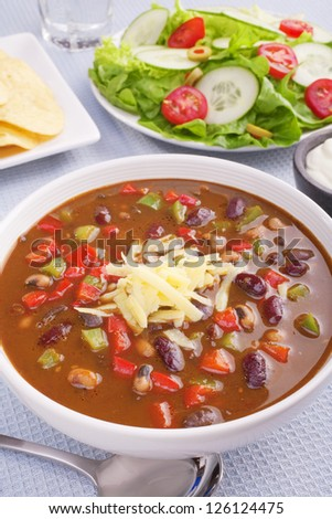 A bowl of hot and spicy soup with colourful vegetables and beans, topped with cheese and served with corn chips, sour cream and salad. - stock photo