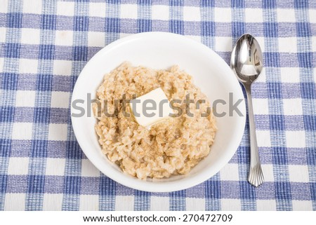 A bowl of hot, fresh cooked oatmeal with melting butter - stock photo