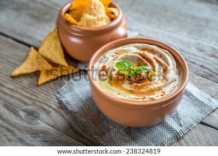 A bowl of hummus with corn chips - stock photo