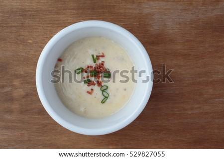 A bowl of loaded potato soup from above garnished with bacon pits and scallions.