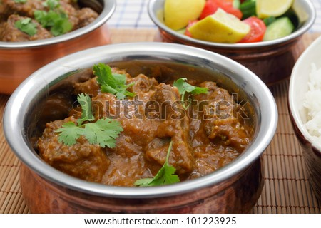 A bowl of Madras butter beef curry with rice, salad and another curry bowl in the background - stock photo