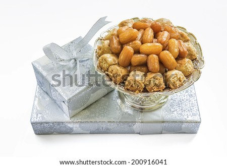 A bowl of middle-eastern sweet is placed on silver color gift boxes - stock photo