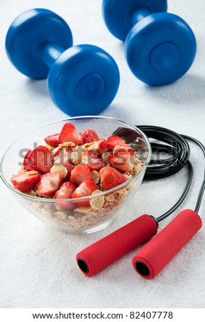 A bowl of muesli with strawberries, a jumping rope and dumbbells - stock photo