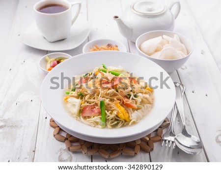 A bowl of noodles with eggs, chicken, tomato, green vegetables served with shrimp crackers, fried shallot, cayenne on rustic white wooden background - stock photo