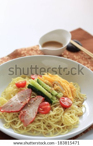 A bowl of noodles with ham and veggies on top plus some dipping sauce. - stock photo