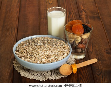 A bowl of oatmeal, a glass of milk and a spoon on a background of dark wood.