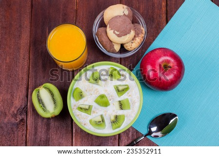 A bowl of oatmeal with slices of kiwi. Oatmeal with yogurt and kiwi fruit on the table. Nutritious vegetarian breakfast. Low-fat diet. - stock photo