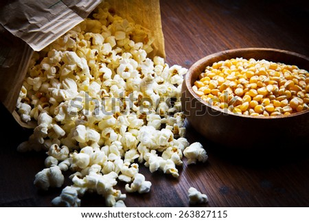A bowl of popcorn and kernels on a wooden table - stock photo