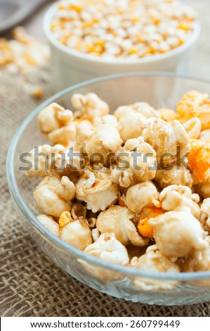 A bowl of popcorn on a wooden table, caramel popcorn - stock photo