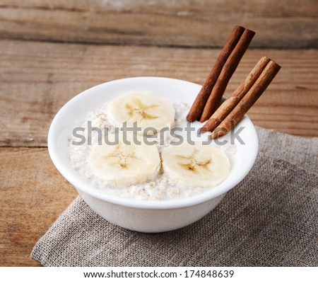 a bowl of porridge with bananas and cinnamon sticks on linen tablecloth on wooden table - stock photo
