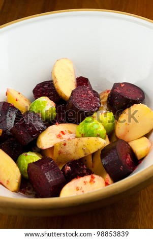 A bowl of raw potatoes, beetroots and brussels sprouts - stock photo