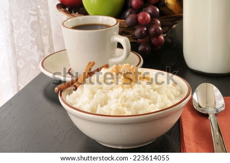 A bowl of rice and milk with brown sugar and cinnamon sticks