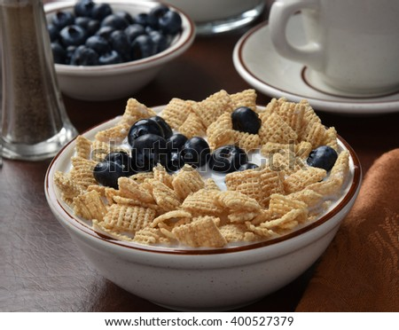 A bowl of rice breakfast cereal with blueberries on top - stock photo