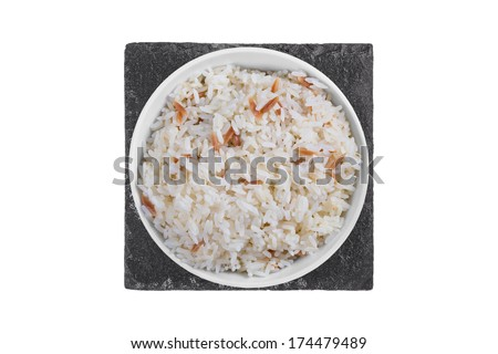 A Bowl of Rice on Black Slate Board Isolated on a White Background - stock photo