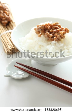 A bowl of rice topped with beans and a pair of chopsticks. - stock photo