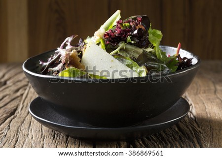 A bowl of salad sitting on an old rustic wooden table. Parmesan, pear and walnut. - stock photo