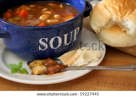 A bowl of soup with a bite full in a spoon laying on a plate. - stock photo
