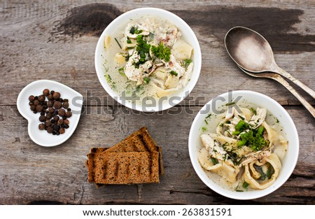 A bowl of soup with noodles and chicken on a wooden table - stock photo