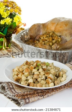 A bowl of stuffing in front of the Thanksgiving turkey. - stock photo
