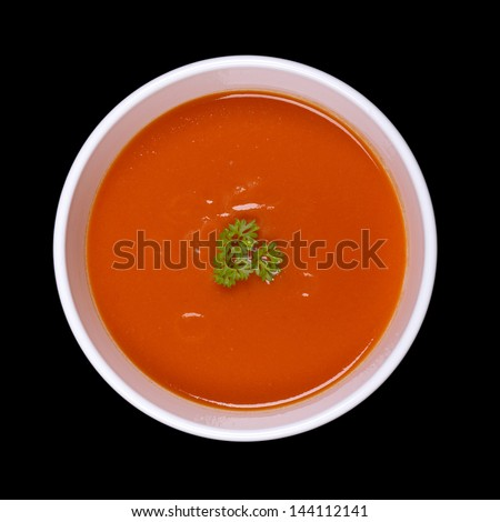A bowl of tomato soup with a parsley garnish, isolated on black background - stock photo
