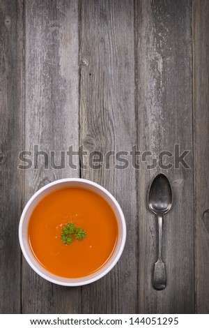 A bowl of tomato soup with a tarnished silver spoon, against a rustic wood tabletop. Vintage style with intentional vignette and selective desaturation and space for your text - stock photo