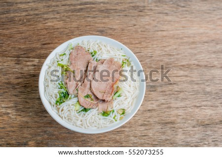 A bowl of Traditional Vietnamese beef soup Pho Bo at the dark old wooden background. ethnic meal. Vietnamese food concept