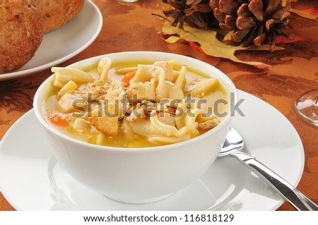 A bowl of turkey noodle soup on a Thanksgiving table