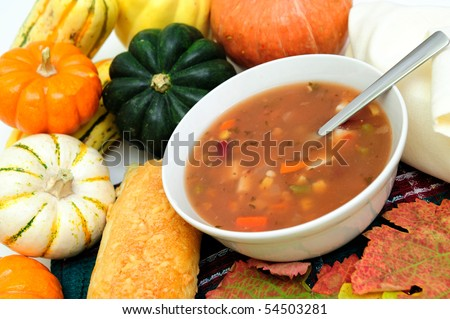 a bowl of warm veggie soup with seasonal Autumn vegetables and colorful fall leaves