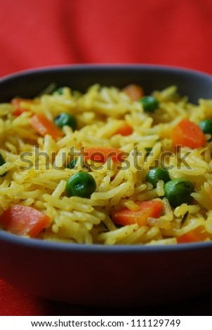 A bowl of yellow oriental rice with carrots, peas, onion and curry - stock photo
