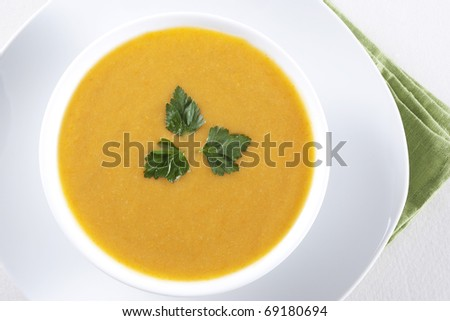 A bowl of yellow soup with parsley