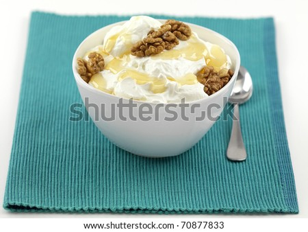 a bowl of yogurt with honey and walnuts on a napkin