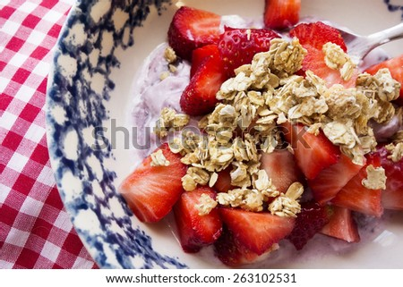 A bowl of yogurt with strawberries and granola on a red and white cloth. - stock photo