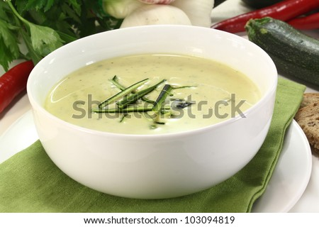 a bowl of zucchini creme soup with fresh julienne - stock photo