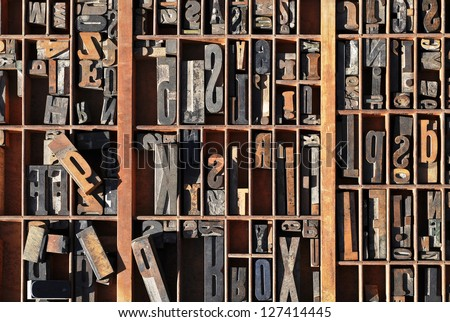 A box of old vintage printing press letter blocks in a old wooden box - stock photo