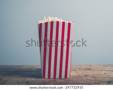A box of popcorn on a wooden table - stock photo