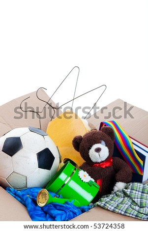 A box of unwanted stuff ready for a garage sale or to donate to a charitable organization.  Generic teddy bear.  Shot on white background. - stock photo