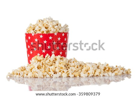 A box with popcorn and stars on the red box isolated on white.Reflecting on the table.  - stock photo