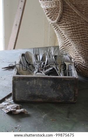 A box with spoons and forks in an old abandoned house - stock photo