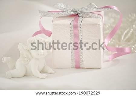 A box wrapped in silver and pink ribbon. - stock photo