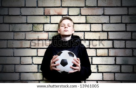 A boy against a wall with a ball